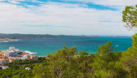 oft: Panoramic hill side view from St Antoni de Portmany, Ibiza, into balearic sea on a clearing day in November, featuring the oft viewed Conejera islands.