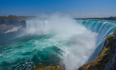 unstoppable: Mighty Niagara River roars over the edge of the horseshoe falls in Niagara Falls Ontario.  Misty foggy spray rises up.