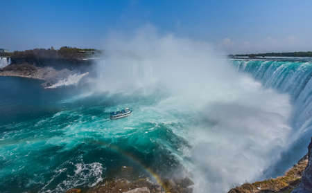 the edge of horseshoe falls: Boat gets soaked at the base of the Mighty Niagara Falls as the River roars over the edge.  Horseshoe falls in Niagara Falls Ontario.  Misty foggy spray rises up.