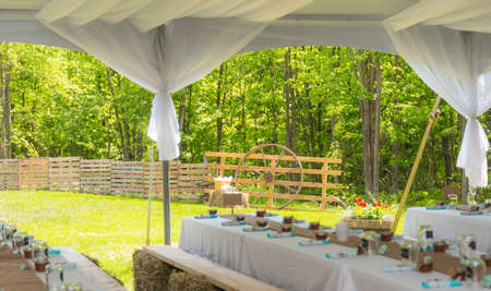 bails: Sunny outdoor country wedding reception dinner party tables ready to receive guests.  Seating on planks atop small hay bails at tables.   Festive Back yard dinner celebration.