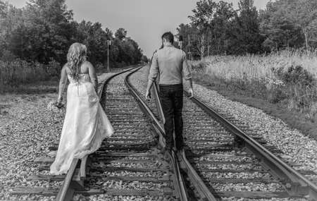 black and white railroad tracks: Newlywed couple walking on the rails of a pair of railroad tracks in black and white.