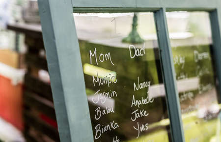 Head Table:  names on a window form a seating plan at a wedding reception dinner.  Country style seating plan for reception dinner.