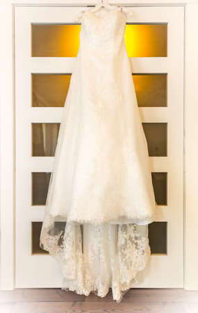 closet door: A wedding dress hangs on a bedroom closet door in warm bedroom light.