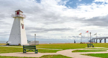 inter: A derelict lighthouse now retired to a park by PEI to New Brunswick, Inter provincial bridge in Canada.   Have a seat on the bench to a view of the bridge on an muggy, overcast summer day in August. Stock Photo