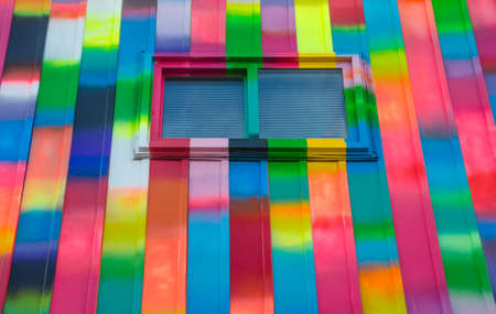 window shades: Abstract colour, bright, rectangular, rainbow coloured window and wall exterior.  Super colorfully bright painted aluminum panelled wall featuring small slider window with blind shades drawn. Stock Photo