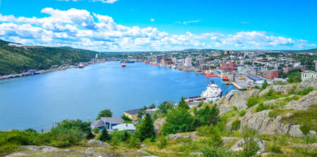 nfld: St Johns Harbour in Newfoundland Canada.  Panoramic view of the city. Warm summer day in August from atop the Historically famous Signal Hill in St. Johns. Stock Photo