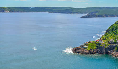 nfld: Summer day over the coastline and cliffs of a Canadian National Historic Site, Fort Amherst in St Johns Newfoundland, Canada. A speeding boat passing through appears slow relative to the vastness.