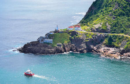nfld: Wonderful view - summer day over the coastline and cliffs of a Canadian National Historic Site, Fort Amherst in St Johns Newfoundland, Canada.  A tour boat passes through. Stock Photo