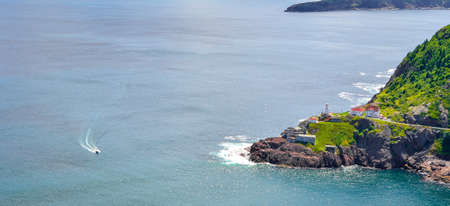 nfld: Boats motor past Fort Amherst.  Rugged coastline and Atlantic ocean. Warm summer day in August with views from atop the Historically famous Signal Hill in St. Johns. Stock Photo