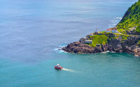 Wonderful view - summer day over the coastline and cliffs of a Canadian National Historic Site, Fort Amherst in St Johns Newfoundland, Canada.  A tour boat passes through. Stock Photo