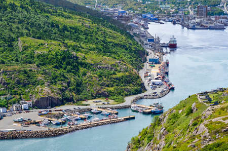 nfld: At the entrance to St Johns Harbour in Newfoundland Canada.  Boats docked in harbour.   Houses at the foot of the mountain, local workplaces.  Views from Signal Hill in St. Johns. Stock Photo