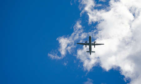 nfld: Blue sky fly-over.   Aircraft on a glide path to the airport in St Johns Newfoundland, Canada.   An airplane passes overhead in sunny blue sky weather landing at the airport in St. Johns, Newfoundland.