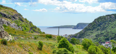 View of Cape Spear, road to Fort Amherst, on the other side of the unseen inlet to St. Johns harbor.  Bright blue sky cloud mix as seen from Signal Hill in St. Johns, Newfoundland.