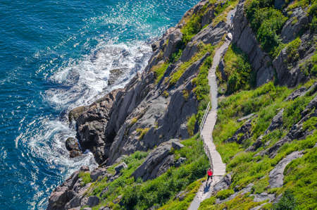 Cabot Trail - Bright summer day - people go hiking along the Cabot Trail in St. Johns Newfoundland, Canada.   View of the Cabot Trail with hikers walking along. Stock Photo
