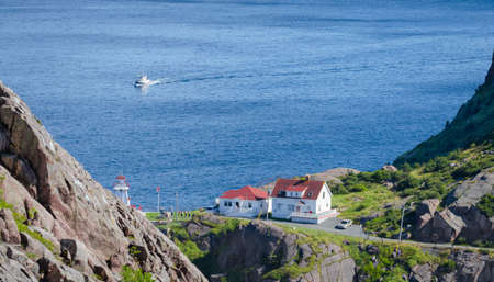 People and tourists visiting the lighthouse on the cliffs of National Historic Site of Canada, Fort Amherst in St John's Newfoundland.  A tour boat passes by.