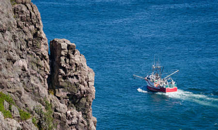newfoundland: Bright red fishing boat heads out to sea on sunny summer day from St. Johns harbor Newfoundland, Canada.