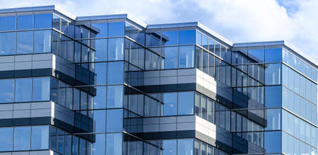 commercial real estate: Lines, glass and reflections of modern architecture.  Glass panelled building of new office space in city of Moncton, New Brunswick.    New commercial real estate in the city of Moncton New Brunswick, Canada. Stock Photo