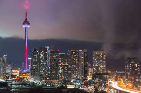 corporate building: Clouds edge cuts through hot humid night time air in Toronto, Canada.  Long exposure of urban illuminated skyline as rain cloud quickly moves in on a hot humid August evening.