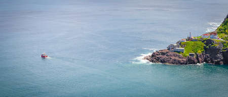 nfld: Sunny summer day over the coastline and cliffs of National Historic Site of Canada, Fort Amherst in St Johns Newfoundland, Canada.  Fishing boat passes by just offshore. Stock Photo