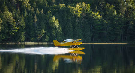 Small yellow airplane on pontoons takes off from an Eastern Ontario lake on a summer's evening.