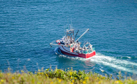 Bright red fishing boat heads out to sea on sunny summer day from St. Johns harbor Newfoundland, Canada.
