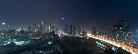 Glowing light streaks from a wet Gardiner Expressway as traffic never stops.  Hot & rainy, muggy summer night in Lakeside Toronto Ontario, Canada. Stock Photo