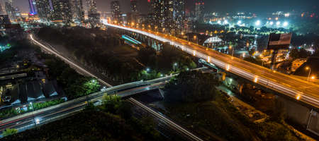 Glow from subway Train as it travels on rails beside the Gardiner Expressway on a hot & muggy summer night in Lakeside Toronto, Canada.  Traffic never stops. Stock Photo