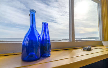 lattice window: Blue bottles in a window beside the sea, Newfoundland Canada. Wide Angle view, Blue glass bottles decorate a shelf at a window with a view to the Atlantic in Grand Bank Newfoundland.