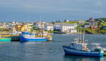 livelihoods: Bona Vista, Newfoundland fishing village.   Boats tied up - in for the day, bright sunshine on calm coastal water. Stock Photo