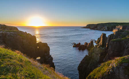 Dramatic sunrise cliffs at Cable John Cove Newfoundland.  Daybreak over Atlantic ocean. Dramatic sunrise August morning summer sun breaks  over the Atlantic in Lancaster and Cable John Cove, Newfoundland, Canada. Stock Photo
