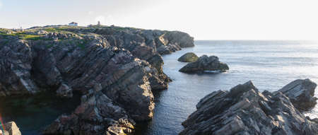 Cape Bona Vista coastline in Newfoundland, Canada.  Lighthouse station atop the end of the cape ahead on the horizon. Stock Photo