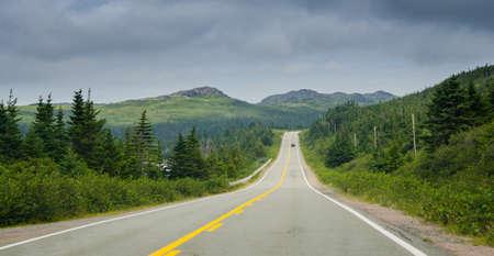 blacktop: Car on a Highway through coastal Foothills of Newfoundland.  Newfoundland highway in overcast skies.  Lone car goes down the road.  Coastal highways in foothills and valley ranges of Newfoundland.