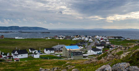 Bonavista, Newfoundland, Canada, on mid summer overcast day.   Village community alongside the sea.  People staying inside on blustery day except one man working on his roof.