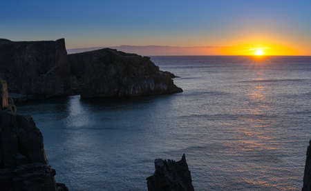 colonnade: Dramatic sunrise on August morning.  Summer sun breaks  over the Atlantic ocean in Lancaster and Cable John Cove, Newfoundland, Canada. Stock Photo