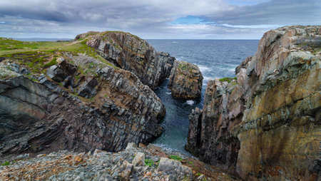 newfoundland: Huge rock & boulder outcrops along Cape Bonavista coastline in Newfoundland, Canada.   Coastal layered slabs of stone and rock that show their layers of formation over millions of years. Stock Photo