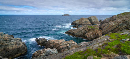 Huge rock & boulder outcrops along Cape Bonavista coastline in Newfoundland, Canada.   Coastal layered slabs of stone and rock that show their layers of formation over millions of years. Stock Photo