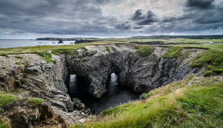 haunting: Dungeon national Park, Newfoundland featuring a rare natural occurrence of rock formation under which, two tunnels comprise a haunting face - earning it its local nickname, Devils eyes.