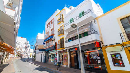 awnings windows: Postcards from Ibiza.  Shops, parlors, cafes and convenience stores line bright sunny streets of Ibizas largest town, take a seat and relax in St Antoni de Portmany Balearic Islands, Spain.