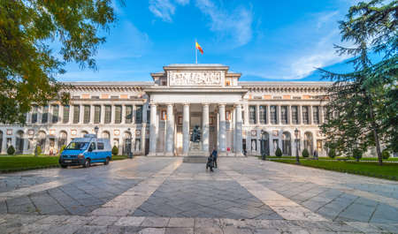 Clear sky, visitors photograph each other in front of The Prado Museum.  Front entrance and terrace to  Museo del Prado, Spanish national art museum, located in central Madrid.