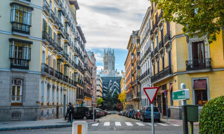 People stroll along in Madrid streets, Single point perspective at a street and pedestrian crossing, yield sign, colourful apartment buildings, street scene.  Urban life, parked cars in street.