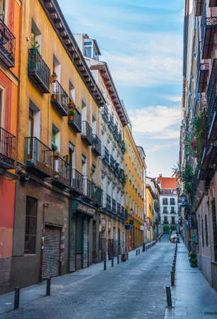 Quiet alley street scene, in Madrid, Spain.  Two women and a child at the far end, crossing the lane.  Colourful tall apartment buildings walls lined the street along with narrow sidewalks.