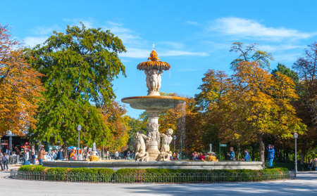Madrid, Spain - November 9th, 2013:    Tourism in Spain.  A fountain is well attended in Retiro Park.  WomanMan takes a photo.  Citizens and tourists alike, take advantage of beautiful weather conditions in The Park of Madrid in the citys core. Editorial