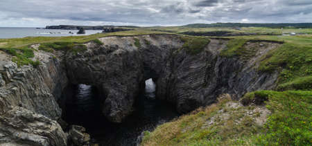 comprise: Devils eyes in Dungeon National Park, Newfoundland, Canada, featuring a rare natural occurrence of rock formation under which, two tunnels comprise a haunting face - earning it its local nickname, Devils eyes. Stock Photo