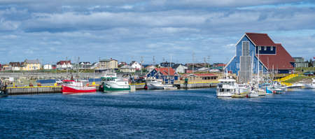livelihoods: Fishing boats docked in villages harbours in Bonavista. Newfoundland, Canada.    Newfoundland fishing villages see boats at rest for the day on calm coastal water.