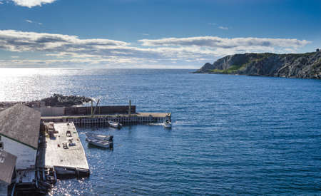 newfoundland: Twillingate, Newfoundland, man works on the engine of one of 4 boats tied up to a wooden, cliff-side dock house for the day, bright sunshine on calm coastal water.