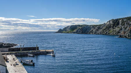 tied in: Boats at a cliff-side dock house in Twillingate, Newfoundland, man works on the engine of one of 4 boats tied up to a wooden, cliff-side dock house for the day, bright sunshine on calm coastal water.