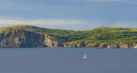 newfoundland: Late afternoon sun shines on an outcropping of high rugged terrain in calm sea water as a sailboat under motor power, goes along in the bay at Twillingate, Newfoundland, Canada.