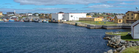 Working day in Bonavista village.  Shoreline View across the water to town in rural Newfoundland, Canada.  People walking along a sidewalk waters edge.