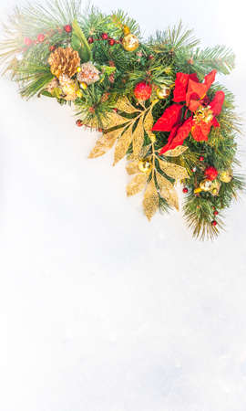 pine wreath: Christmas holiday faux poinsettia pine wreath adorned with gold leaf ribbon, Christmas balls and holly, resting on natural snow with white copy space. Stock Photo