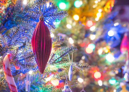 Christmas tree decorations.  Glowing red christmas holiday tree ornaments hanging from branches on a small faux indoor holiday christmas tree adorned with multicolored mini lights. Stock Photo